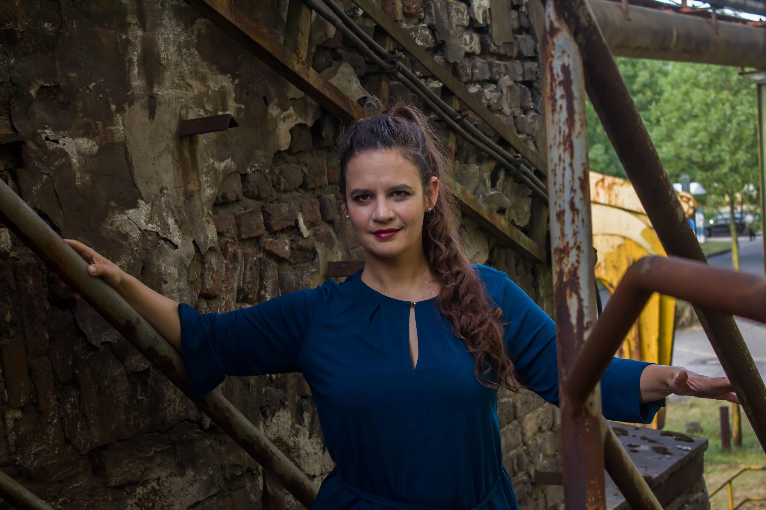 Hanna steigt eine Treppe an einem heruntergekommenen Industrial-Bau empor und lächelt die betrachtende Person an.