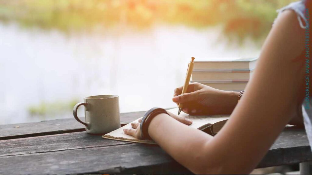 Eine Frau schreibt auf die erste Seite eines Buches. Sie sitzt an einem abgenutzten Holztisch an einem See. Neben ihr steht eine Tasse Kaffee.